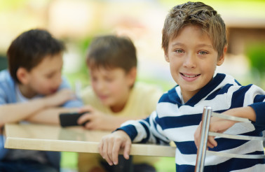 Portrait of smiling boy in cafe with his friends in the background